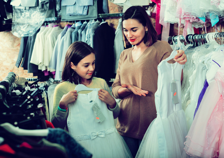 acquiring: Satisfied  smiling mother and daughter choosing pretty dress in children's cloths shop Stock Photo