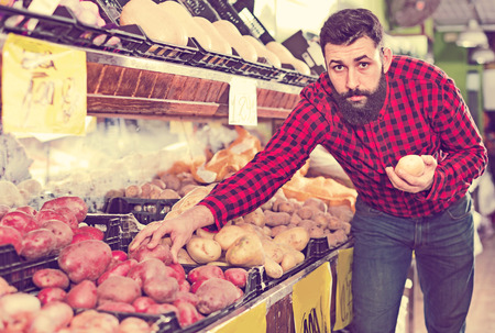Young  positive male seller offering potatoes in grocery shop Stock Photo