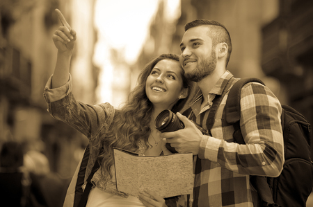 Smiling tourist couple going sightseeing with camera through square of European city