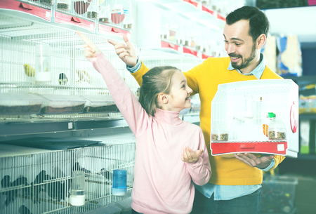 buying time: Portrait cheerful father and daughter choosing pretty bird for keeping in pet shop