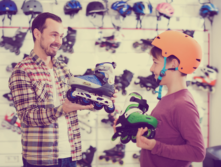 acquiring: Laughing father and boy boasting purchased roller-skates in sports store Stock Photo