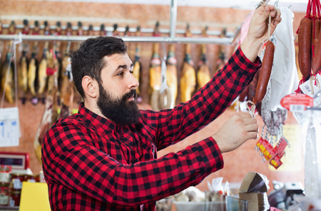 Young smiling male customer examining sausages in butcher's shop