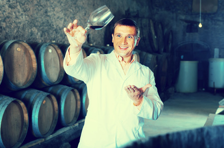 laboratorian: smiling factory sommelier in white robe checking quality of red wine in cellar with barrels
