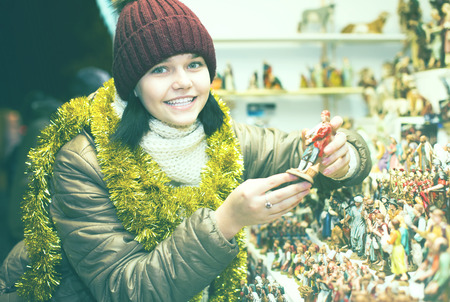creche: Nice teen girl  with figures for creating  miniature Christmas scenes   at  Christmas market Stock Photo