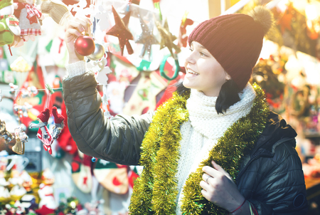 overspending: teen customer near counter with Christmas gifts at fair Stock Photo