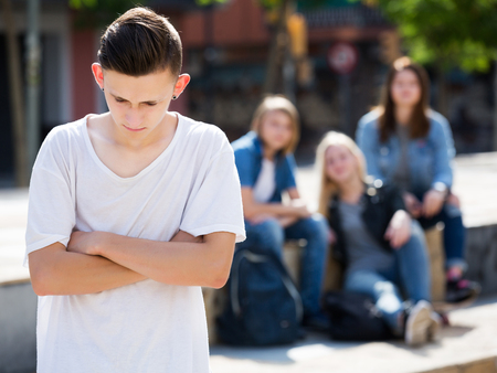 misfit: Lonely sad male teenager standing away from friends feeling depressed Stock Photo