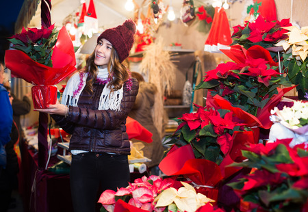 Young smiling teenager girl staying near counter with poinsettia at Christmas market
