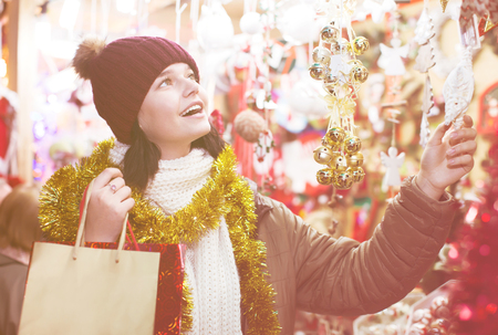 Ordinary female customer near counter with Christmas gifts