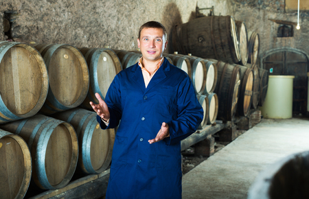 laboratorian: Positive adult man in robe checking ageing barrel process of wine