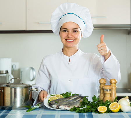 cartilaginous: Cheerful professional chef cooking fresh mackerel at kitchen table Stock Photo