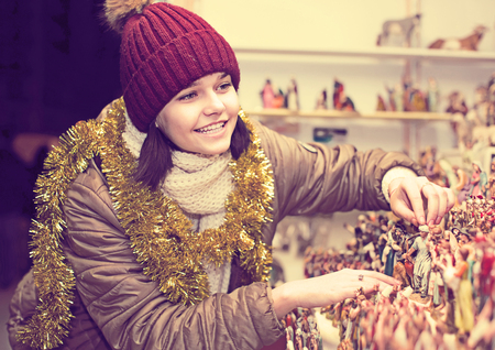 creche: smiling female customers staring at counter of kiosk with figures for creating  miniature Christmas scenes Stock Photo