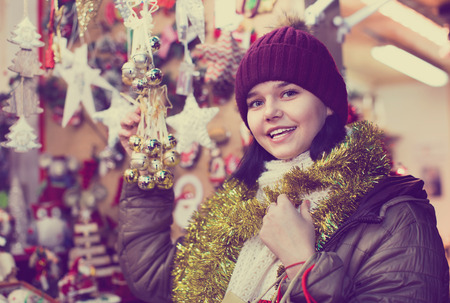 Smiling satisfied friendly pleasant teenage girl shopping at festive fair before Xmas