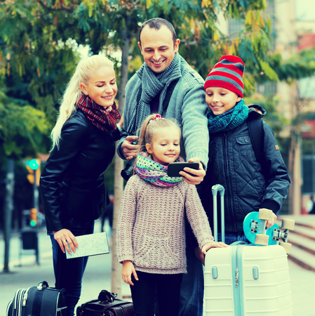 5s: Parents with two kids and baggage taking a selfie on smartphone Stock Photo