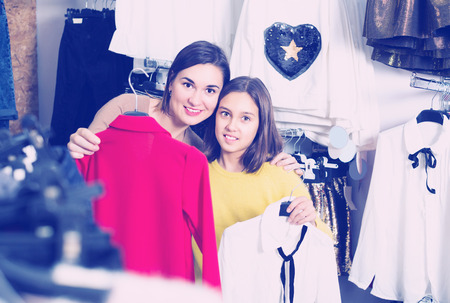 boasting: Mother and daughter are boasting by their purchases in children�s clothing shop. Stock Photo