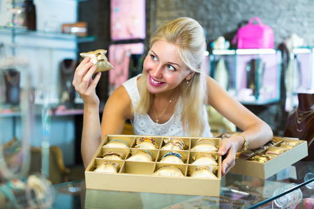 smiling young female jeweler showing fashion bracelets in bijouterie boutique Stock Photo