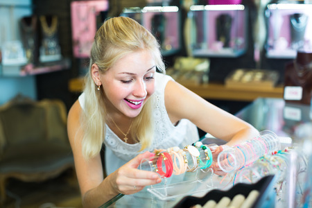 excited smiling blonde girl selecting new bracelet in bijouterie shop