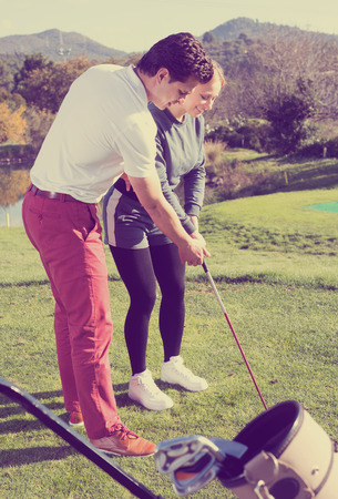 Positive man golf trainer showing woman player how to hit ball rightly