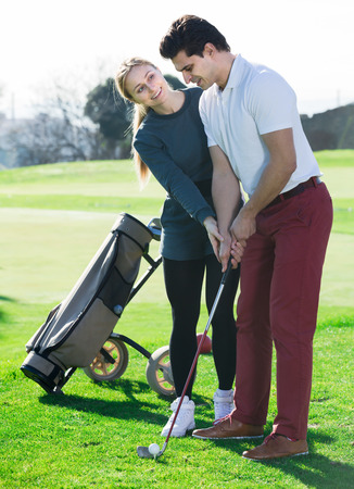 Ordinary golf trainer showing male player how to hit ball rightly