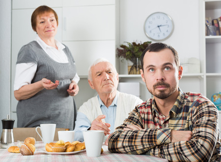 Father and mother having disagreement with adult son at home