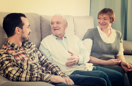 three generations of women: Grandfather and grandmother warmly conversation with grandson at home on couch