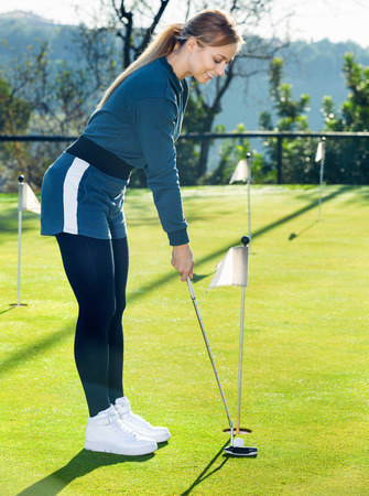 brassy: Female golf player getting ready to hit ball at golf course Stock Photo