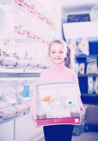 Smiling girl customer enjoying her purchase of canary bird in pet shop Stock Photo