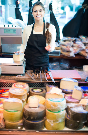 happy female brunette with different types of cheese in gastronomy