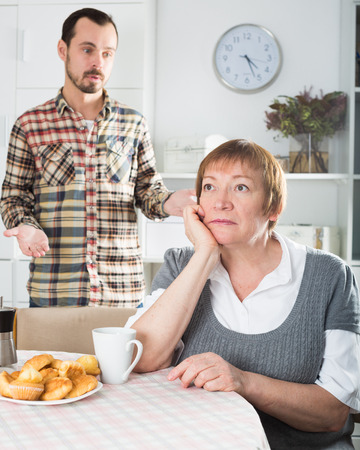 Son defends his position before adult mother at home Stock Photo