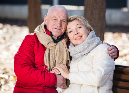 attachment: Aged husband and wife sitting together on bench in park on chilly day Stock Photo
