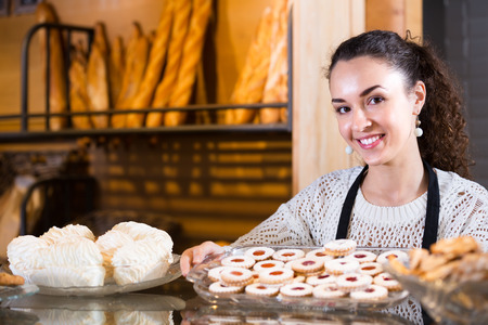 Hospitable friendly girl with delicious cream pies at bakery display Stock Photo