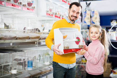 Young father with his daughter chose a canary bird as a new pet in shop