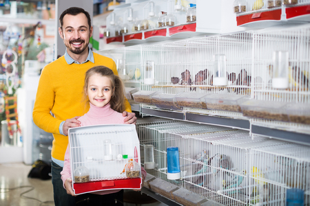 adult father and daughter enjoying their purchase of canary bird in pet shop