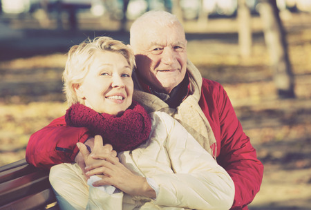 Senior couple sitting on bench and embracing in park Stock Photo