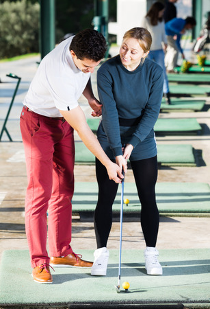 brassy: Golf Coach tells a young girl how to hit the golf ball