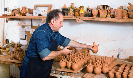 Smiling positive potter at the workshop Stock Photo