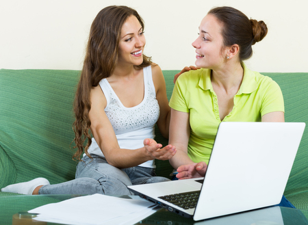 parsimony: happy women looking financial documents with laptop  in home interior Stock Photo