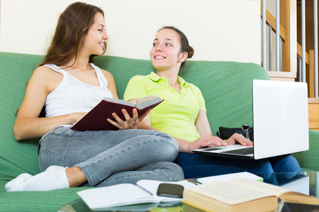 cognate: Smiling young students working on laptop at home Stock Photo