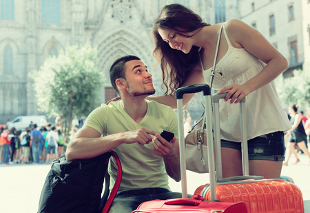Happy young couple in shorts with GPS navigator and baggage outdoor