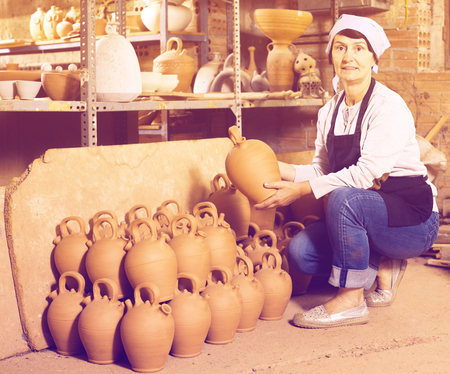 Glad mature female master among the finished products in the pottery workshop