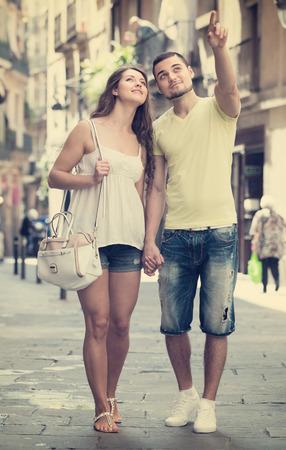 Smiling travelers couple walking through ancient European city