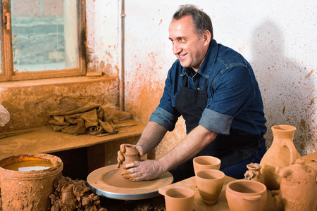 Elderly positive  master among the pottery at the workshop