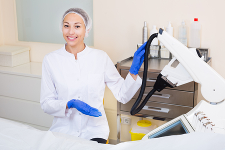 Young female doctor demonstrating the equipment for laser hair removal