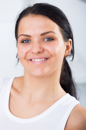 Young brunette woman in white standing in room and smiling