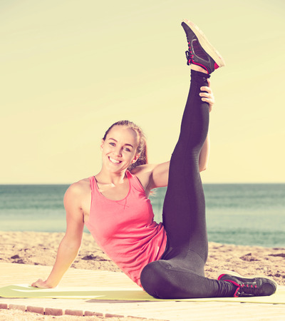 Charming young woman exercising on exercise mat outdoor at the seaside