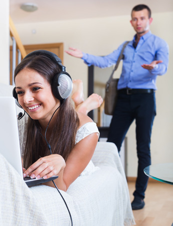 Upset husband blaming wife in internet addiction at a home Stock Photo