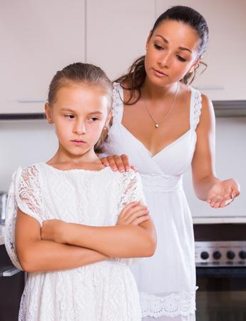 shaming: Crisis of motherhood: sad young woman preaching upset little daughter