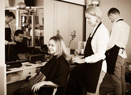 16s: Mature woman cuts hair of blonde girl in barbershop