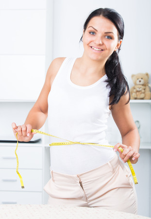 russian ethnicity caucasian: Young brunette woman measures waist by measuring tape