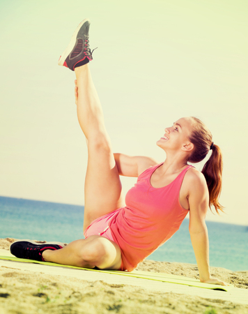Smiling young sporty woman exercising at sea beach