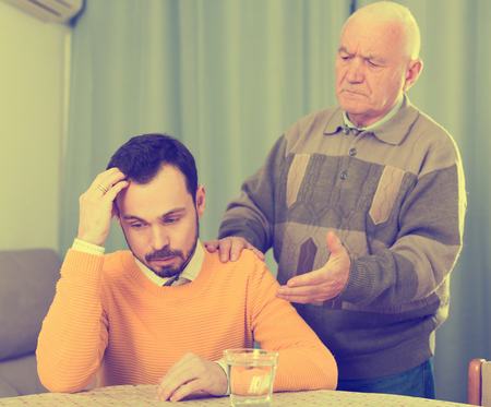 Old father is serious conversation with his son at home